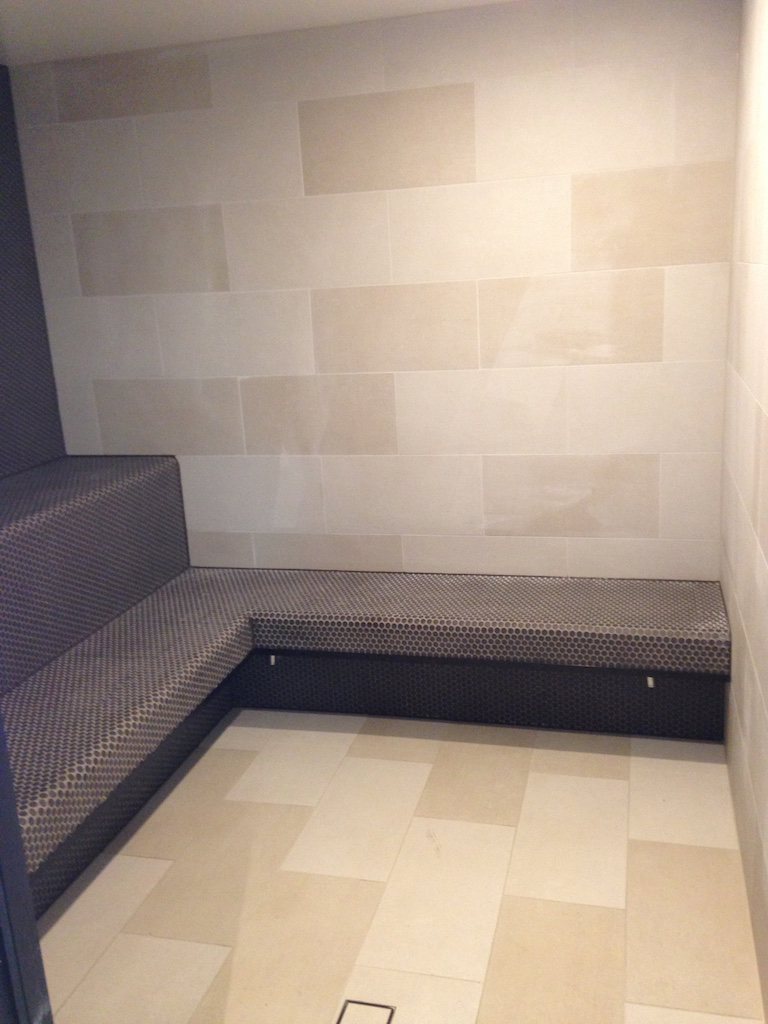 Penny Round Tiles on Benches and Curved Side Wall Inside a Sauna